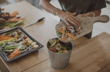 A woman is brushing kitchen scraps off of a cutting board into a bucket