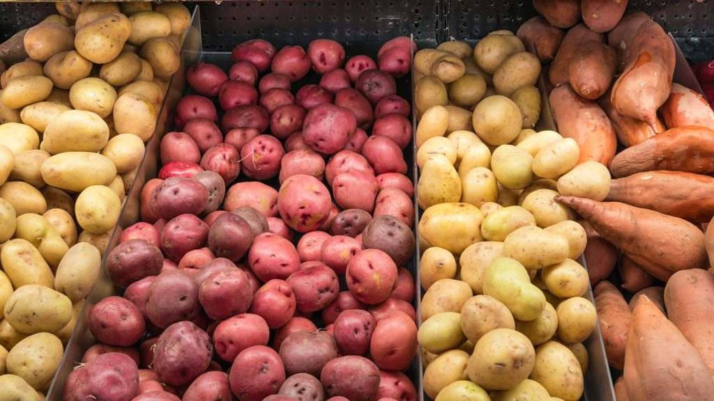 A bunch of different types of potatoes in a grocery store