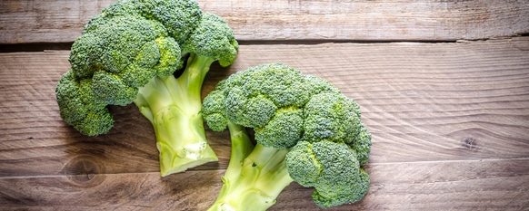 Freshly cut broccoli on a slab of wood
