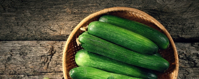 Harvested cucumbers sitting in a wooden bowl