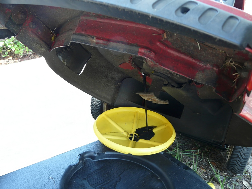 Draining old oil from a lawnmower that is propped up.