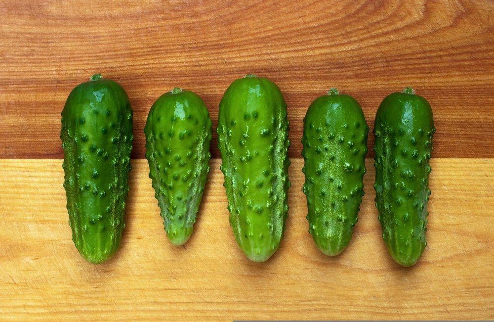 5 picklebush pickles laying on a wooden table