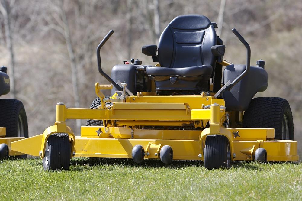 A yellow, zero turn lawn mower sits on a yard