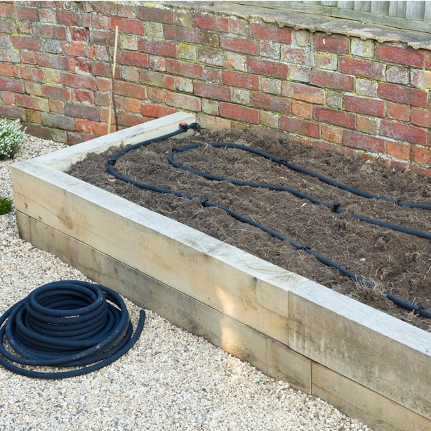 Soaker hose laid in a raised planter snaking in an appropriate pattern
