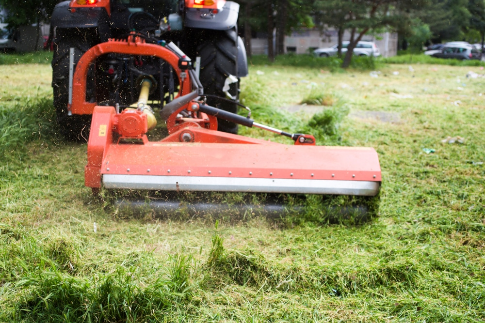A red tow behind lawn mower is cutting grass as it is tugged along.